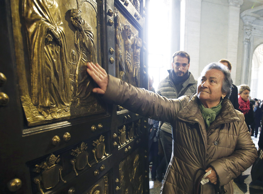 A woman touches the Holy Door in St. Peter's Basilica after Pope Francis opened it to mark the inauguration of the Jubilee Year of Mercy at the Vatican. (Photo © Catholic News Service/Max Rossi, Reuters)