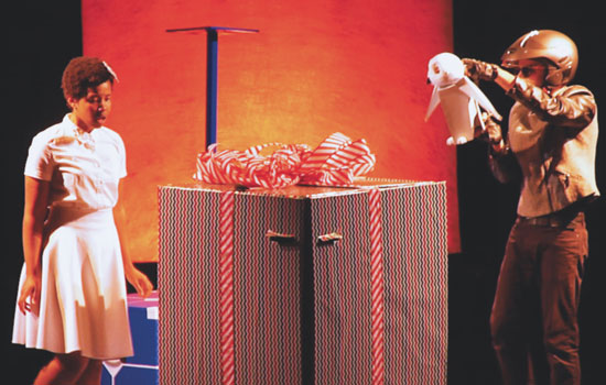 "South African-born actress Kineta Kunutu stars as Liv, above, left, in Stages on the Sounds' play, ""Robot 4 Christmas."" In this scene, she and her owl, Hoolie, played by actor Mauricio Pita, find a mysterious gift addressed to her."