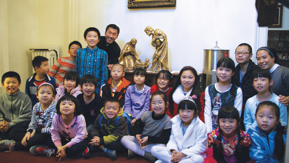 Father Vincentius Do is shown with some of the Chinese immigrant children enrolled in the religious education program at St. Agatha's parish, Sunset Park.