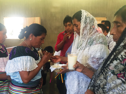 The wife of an indigenous deacon distributes Communion during a Jan. 16 service in a settlement in Mexico's southern Chiapas state. The hosts were consecrated prior to the service by a Jesuit priest. (Photo © Catholic News Service/ David Agren)
