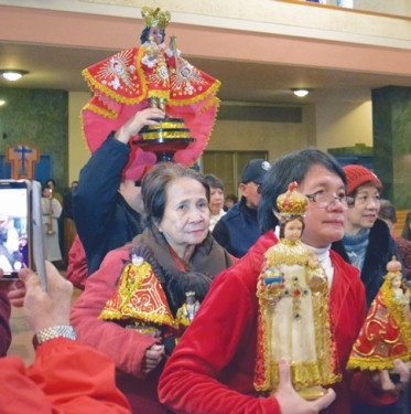 Devotees processed into the church carrying replicas of the Santo Niño statue, which were later blessed.