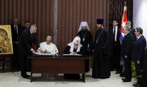 Pope Francis and Russian Orthodox Patriarch Kirill of Moscow sign a joint declaration during a meeting at Jose Marti International Airport in Havana Feb. 12. Standing in front of Cuba's flag is Cuban President Raul Castro. (CNS photo/Paul Haring)