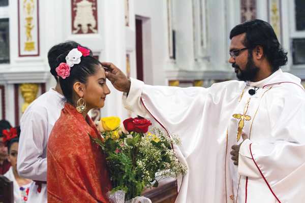 Father Robert Ambalathingal, pastor of St. Pius V, Jamaica, offers a blessing to one of his parishioners. He describes the parish as multi-ethnic with Mass offered in English, Spanish, and Portuguese.