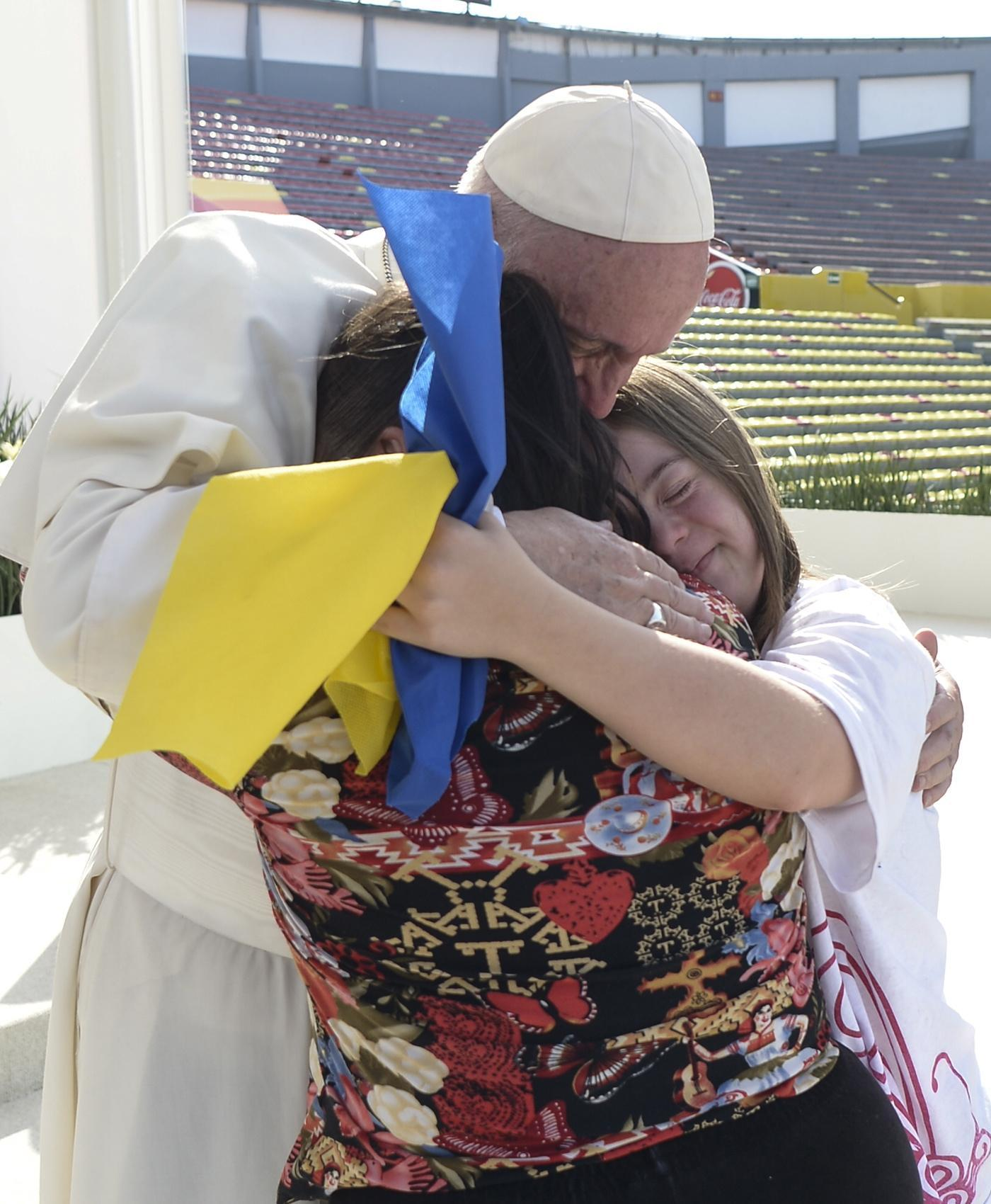 Pope Francis embraces women during a meeting with young people at Jose Maria Morelos Pavon Stadium in Morelia, Mexico, Feb. 16. (CNS photo/L'Osservatore Romano via EPA)