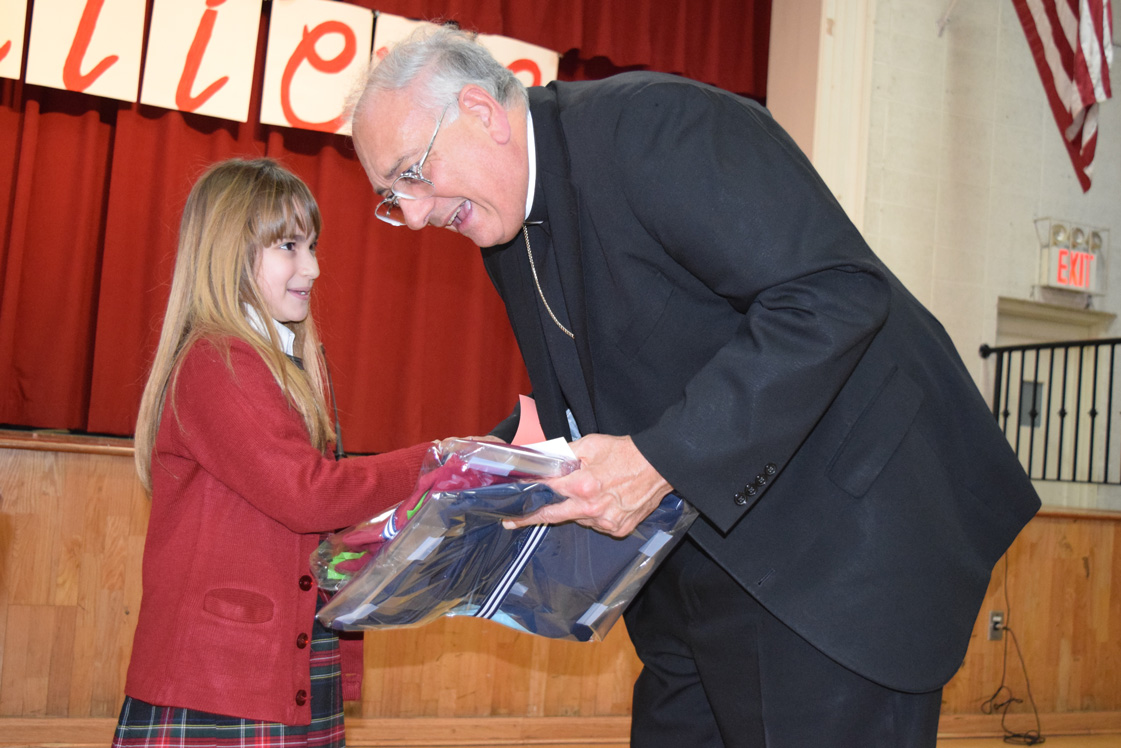 Rinat Moshel, second grader at St. Joan of Arc School, gives presents to Bishop Nicholas DiMarzio to commemorate his visit to the school on Feb. 5. The school's 488 students offered special performances showcasing their talents and love for the school during the bishop's visit. (Photos © Maria-Pia Negro Chin)
