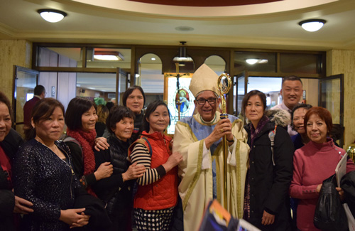 Bishop Octavio Cisneros is greeted by members of the Chinese ministry from St. John Vianney parish, Flushing. (Photo © Maria-Pia Negro Chin)