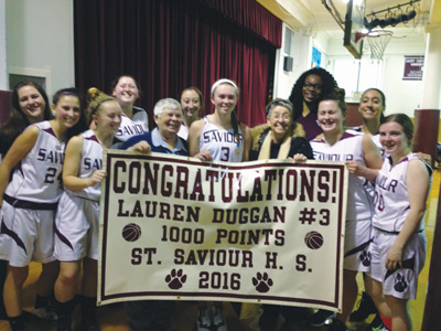 p St. Savior's Lauren Duggan, center, No. 3, scored her 1,000th point on Feb. 5. The school presented her with a commemorative banner.
