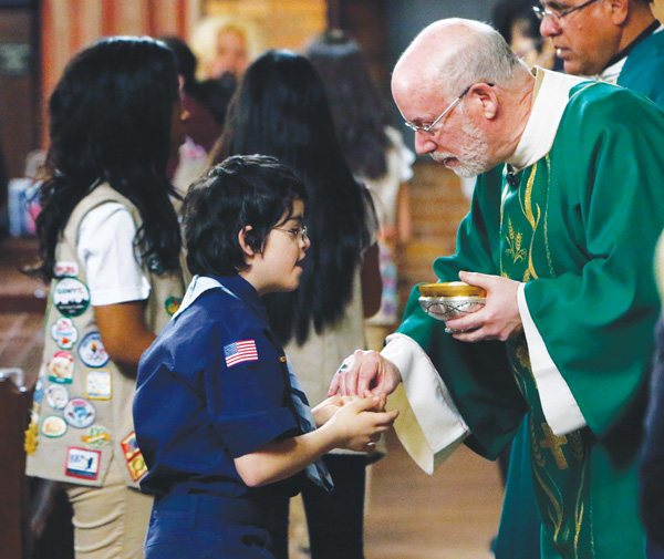 Cub Scout Joey Arden, 8, receives Communion from Deacon Jim Noble, a former Boy Scout, during a Scout Sunday Mass at Immaculate Heart of Mary Church in Windsor Terrace. (Photo © Gregory A. Shemitz)