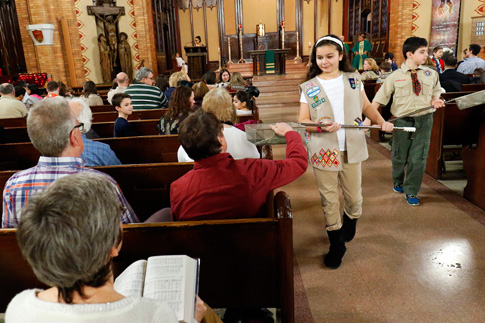 Girl Scout Julia Ocasio, 13, and Boy Scout Thomas Perotta, 10, use collection baskets during a Scout Sunday Mass Feb. 7 at Immaculate Heart of Mary Church in the Windsor Terrace neighborhood of the New York borough of Brooklyn. (Photo © Gregory A. Shemitz)