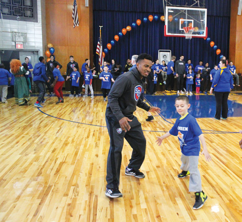 A member of the St. Francis College men's basketball team puts a youngster from St. Ephrem's parish through some hoops drills during the annual Swish for Kids event at the parish gymnasium. (Photo © Jim Mancari)