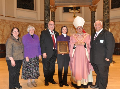 Bishop Cisneros is joined by Ken Latham and Louis Pepe, fourth-degree members of the Knights of Columbus, as he presents the Pro Vita Award to Patricia Caffrey, RN, and other Calvary Hospital staff members.