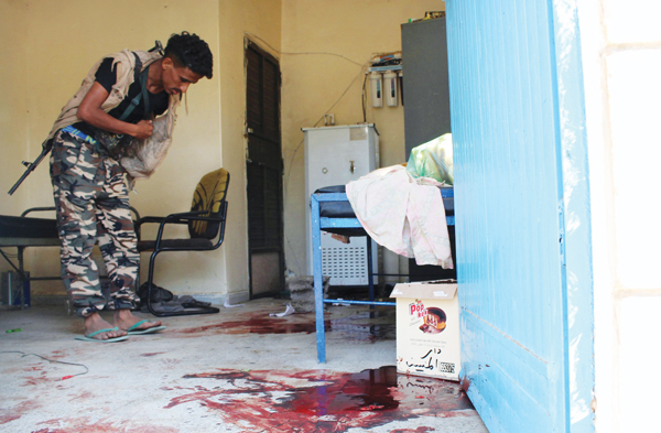 A pro-government militant inspects a room filled with blood after it was attacked by gunmen in Aden, Yemen, March 4. Photo © Catholic News Service/ Stringer, Reuters