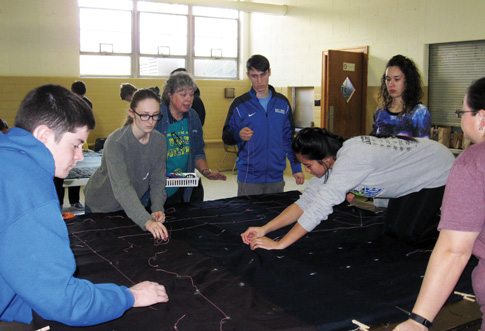 Students and staff from St. Francis Prep, St. Anthony H.S., South Huntington, and Notre Dame R.H.S. help make emergency sleeping bags for those who are homeless. (Photo © Robert Johnston)