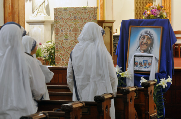 A sister prays before a shrine to the Order's founder, Blessed Mother Teresa of Calcutta, and the four slain missionaries.