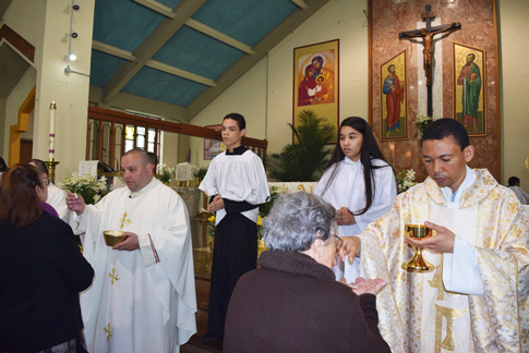 Msgr. Anthony Hernandez, administrator, and Father Juan Rosario, parochial vicar, distribute Communion during the last Mass celebrated in SS. Peter and Paul Church, Williamsburg. (Photos by Maria-Pia Negro Chin)
