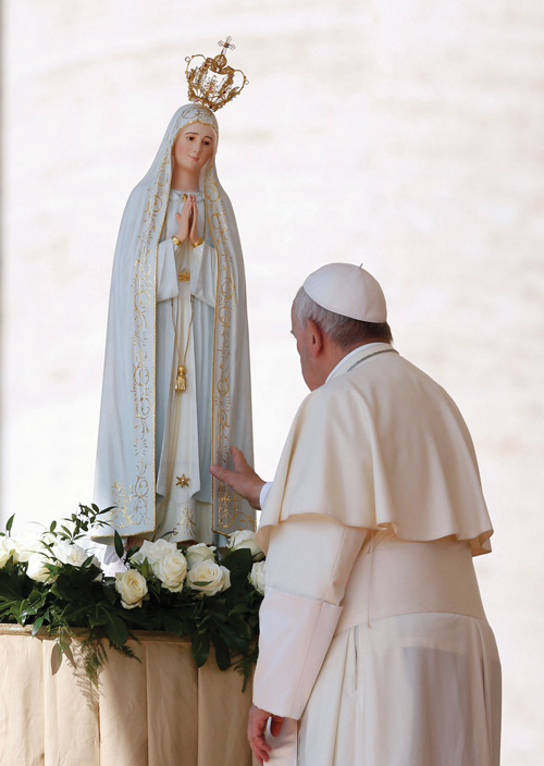 Pope Francis touches a statue of Our Lady of Fatima after praying in front of it during his general audience in St. Peter's Square at the Vatican May 13, 2015. The statue, which was present for the May 13 feast of Our Lady of Fatima, is a copy of the original in Fatima, Portugal. It is similar to the one that will be present in the Diocese of Brooklyn from May 19 to May 23. (Photo © Paul Haring)