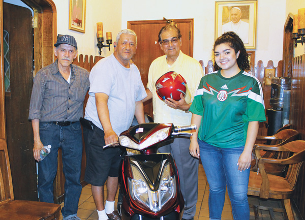 Alejandrina Ochoa, right, poses with members of the Knights of Columbus at St. Brigid Church, Bushwick, as they bring a donation to the parish's World Youth Day pilgrims. The motor scooter will be raffled as part of the group's fundraising efforts.