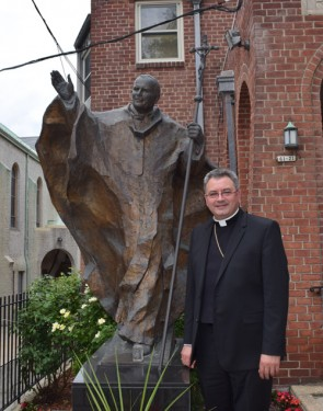 p Bishop Mroziewski poses in front of Pope John Paul II statue at Holy Cross rectory, Maspeth.
