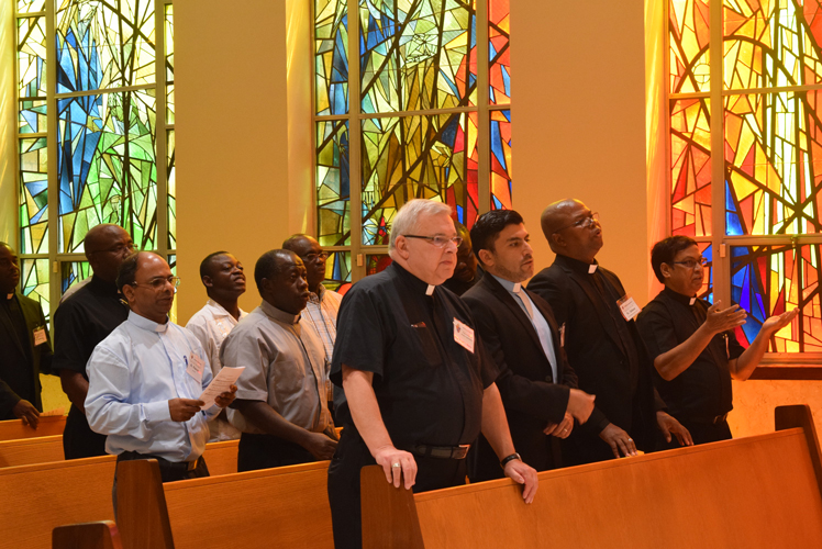 Msgr. Ron Marino, vicar for ethnic apostolates, and priests from foreign lands, attend Mass at the Chancery building chapel as part of a day of workshops for visiting priests.