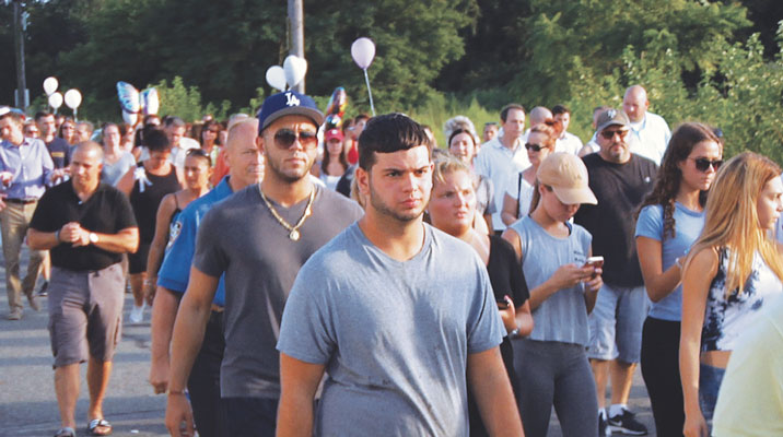 Two weeks after the battered body of 30-year-old Karina Vetrano was found in dense weeds at Spring Creek Park, Howard Beach, mourners walked in honor of the young jogger.