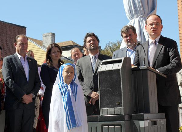 Bronx Assemblyman Mark Gjonaj, the son of Albanian immigrants, far left, and Julia Balaj, dressed as St. Teresa of Calcutta, look on as Albanian President Bujar Nishani addresses the crowd on the corner of Bay Pkwy. and 62nd St. in Bensonhurst.