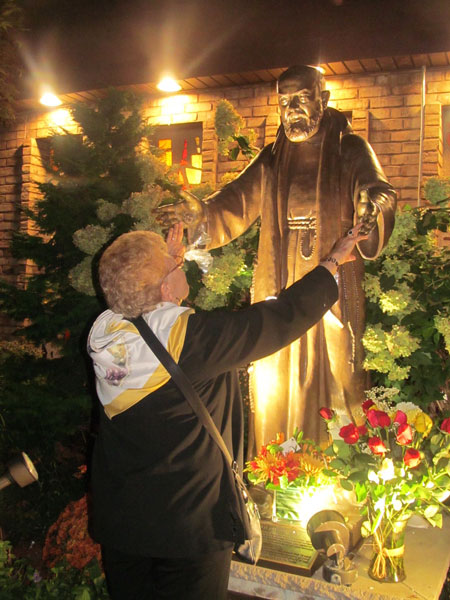 Friday, Sept. 23 marked the end of a Triduum in honor of St. Padre Pio at St. Helen Church, Howard Beach. Mass was followed by a candlelight procession to the shrine of St. Pio, ending with personal veneration of the saint's relic.  Above, Jenny Taranto, one of the organizers, visits the shrine.