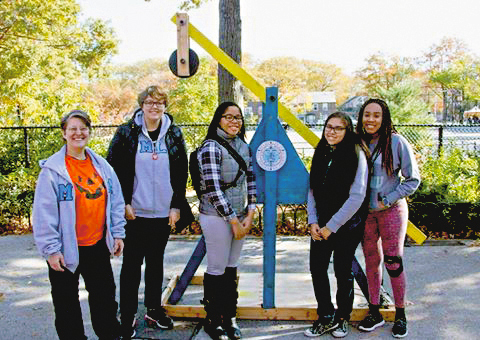 "Young women from the Engineering Program at The Mary Louis Academy, Jamaica Estates, were invited to custom build a trebuchet to take part in the Queens Botanical Garden's 2016 Pumpkin Smash. The students were responsible for the concept, design and actual construction of the medieval siege engine, which required mathematical calculations and formulas to determine weights, counterbalance and velocity. The Pumpkin Smash is an annual event where children and adults bring their ""retired"" Halloween pumpkins and gourds to be smashed via a trebuchet. Once the event is finished the NYC Compost Project turns the smashed pumpkins into compost for city parks and green spaces."
