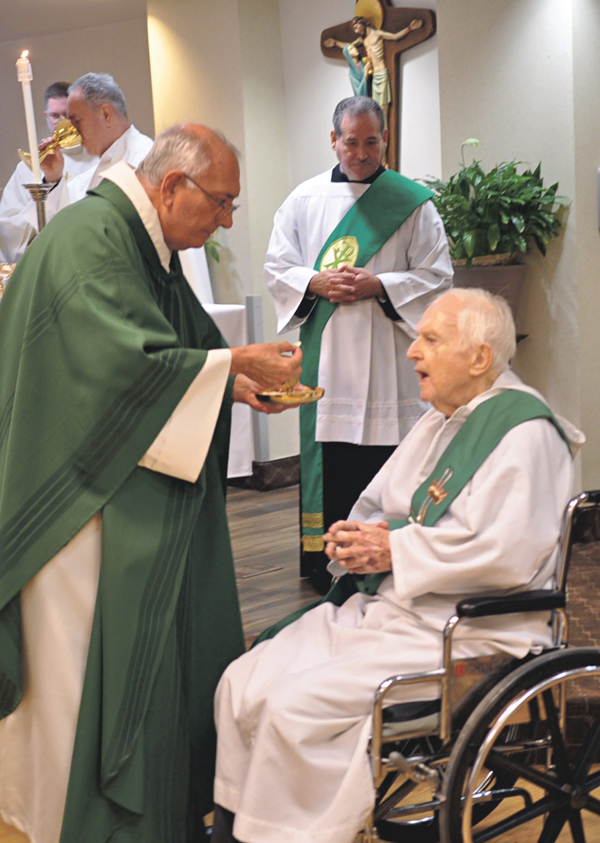 Bishop Nicholas DiMarzio distributes Communion Oct. 23 to Deacon John Dennehy during Mass at a pastoral visit to SS. Joachim and Anne Rehabilitation and Nursing Center, Coney Island. The deacon died Nov. 2.
