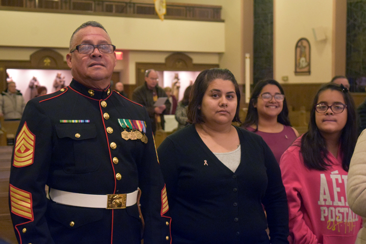 1st Sgt. Sergio Gallardo, who served in the U.S. Marine Corps from 1976 to 1996, with his family during Mass at SS. Simon and Jude