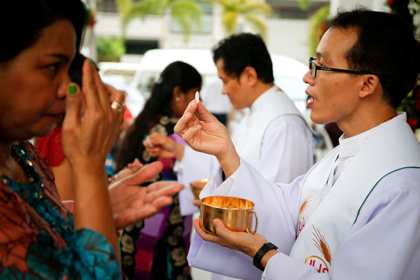 Faithful receive Communion in Bangkok Dec. 25, 2015. Four cardinals said they formally asked Pope Francis to clarify his teaching on Communion for the divorced and civilly remarried and have not received a response in two months. (Photo: Catholic News Service/Diego Azubel, EPA)