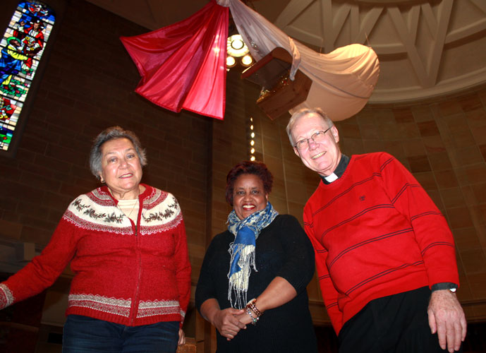 Handmade angels have been appearing each Sunday of Advent at Immaculate Conception Church, Jamaica Estates, to open people's minds and advance the sacredness of the season. From left, parishioners Mireille Leys and Ann Regbeer have brought the angels to fruition under the guidance of Father William Murphy, C.P. pastor. (Photos: Marie Elena Giossi)