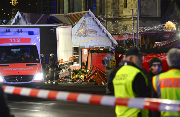 Rescue workers inspect the scene where a truck crashed into a Christmas market in Berlin Dec. 19. The terrorist attack killed at least a dozen people and injured nearly 50 as it smashed through tables and wooden stands. (Photo: Maurizio Gambarini, Reuters)