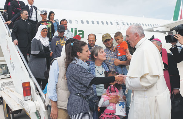 Pope Francis greets Syrian refugees he brought to Rome from the Greek island of Lesbos, at Ciampino airport in Rome April 16, 2016. The pope concluded his one-day visit to Greece by bringing 12 Syrian refugees to Italy aboard his flight. (Photo: Catholic News Service/ Paul Haring)