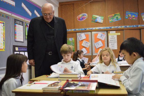 bishop looks over shouldder of stdue nt