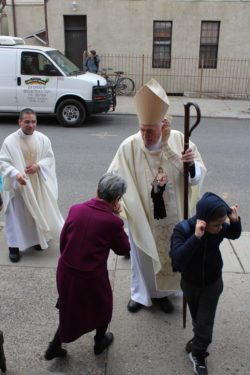 bishop greets old lady outside