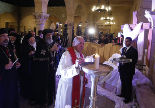 Pope Francis, accompanied by Coptic Orthodox Pope Tawadros II,  lights a candle outside St. Peter's Church in Cairo April 28. The pope lit the candle in remembrance of victims of a December 2016 bombing inside the church. (CNS photo/Paul Haring)