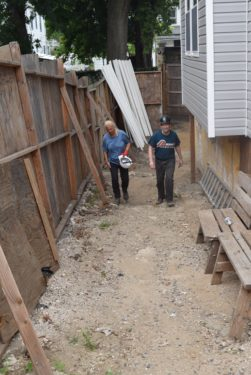 Deacon Bill and Maria Caterinicchio survey the side of the home.