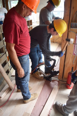 Christopher Andreov helps to put down flooring for the main level of the home.
