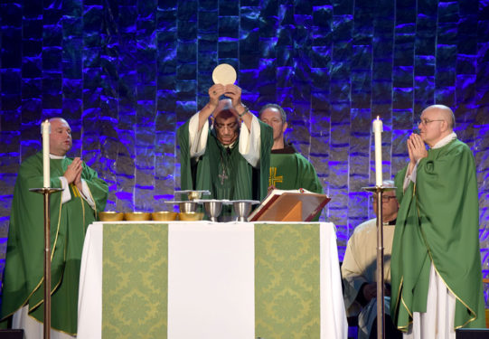 Bishop Nicholas DiMarzio raises the Blessed Eucharist during a mass attended by more than 1,200 people from the tri-state area, Canada and Spain.
