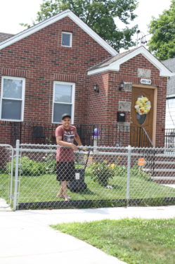 A proud homeowner mowing his lawn at a former Habitat for Humanity home in Queens inspires current volunteers.