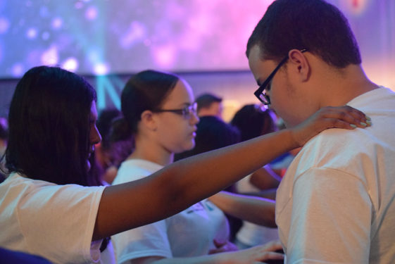 During a special moment to pray for each other, teens from the Presentation of the Blessed Virgin Mary, Jamaica, place their hands over their friends for prayer.
