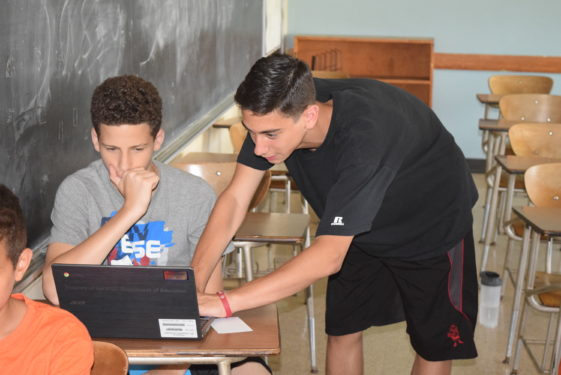 Counselor Anthony Leone, above, an incoming junior at Cathedral Prep and Seminary, Elmhurst, helps a student participating in the Prep's Father Troike Summer Leadership Program with his classwork assignments for the week.