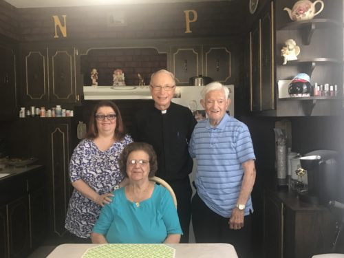Nicholas and Nancy Pennetti of St. Leo's parish, Corona, are congratulated on their 74th anniversary of married life by their pastor, Father William Hoppe, and their  daughter, Nancy