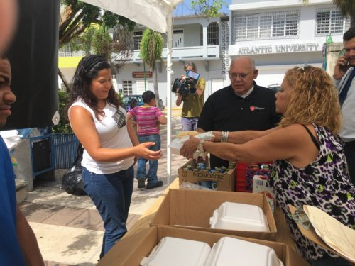 With the destruction of the hurricane evident all around, food is  distributed at the makeshift stand set up by the Knights of Malta.