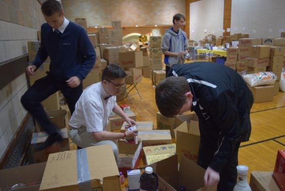 Students from Cathedral Prep and Seminary help pack and sort material goods collected by Catholic Charities for the victims of the  hurricane damage in Puerto Rico.