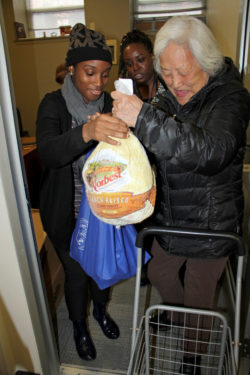 Liu Man Yan, right, was one of nearly 1,000 New Yorkers to receive Thanksgiving turkeys and trimmings from Catholic Charities Brooklyn and Queens. Catholic Charities staffer Cassandra Seide helped to distribute the turkeys in Fort Greene.
