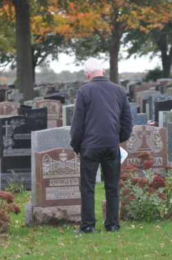 man stands by grave