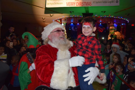 Santa puts a smile on face of a youngster at Christmas party hosted by Reaching Out.