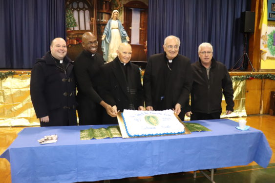 Bishop DiMarzio was invited to cut the cake during a social gathering after Mass. He held the cake up for a picture together with: Deacon James Maloney, who serves the parish; Father Sansone; Father Mark Bristol, who spent a summer in formation at the parish before he was ordained to the priesthood; and Father Sean Suckiel, the diocesan director of vocations who grew up in the parish.