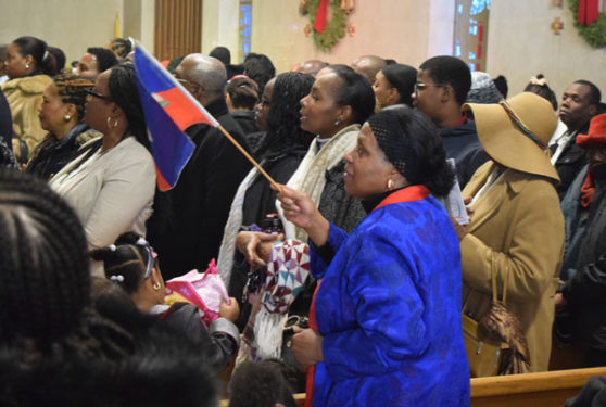 A woman proudly waves her Haitian flag during the Mass...